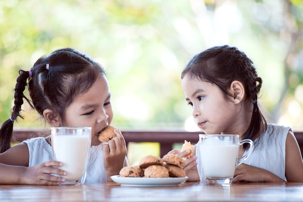 Two cute asian little girls are eating cookies with milk for breakfast