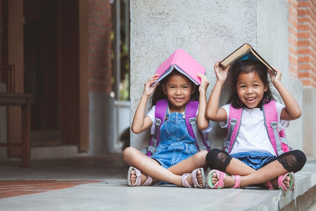 Two cute asian pupil girls reading a book  together in the school with fun and happiness