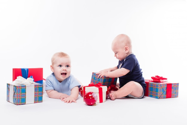 Two cute baby sitting among the christmas gift box