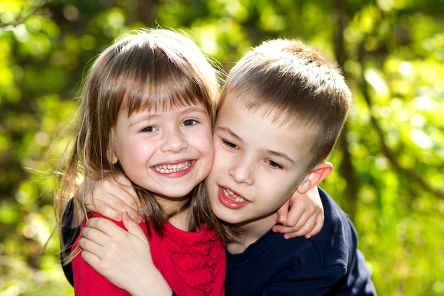 Two cute blond funny happy smiling children siblings, young boy brother embracing sister girl outdoors on bright sunny green bokeh . family relation, friendship and love .