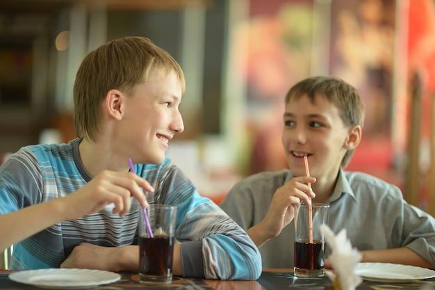 카페에서 콜라를 마시는 두 귀여운 소년
