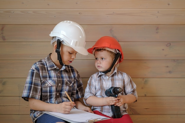 건설 헬멧을 쓴 두 명의 귀여운 소년이 다가오는 작업에 대한 계획을 논의하고 있습니다. 아이들은 건축업자를한다. 그의 손에 드라이버와 어린 소년