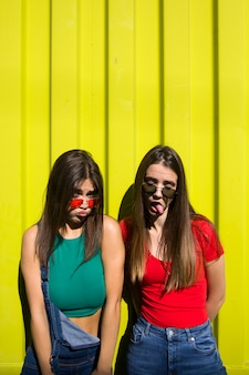 Two cute casual young women fooling around in front of yellow wall
