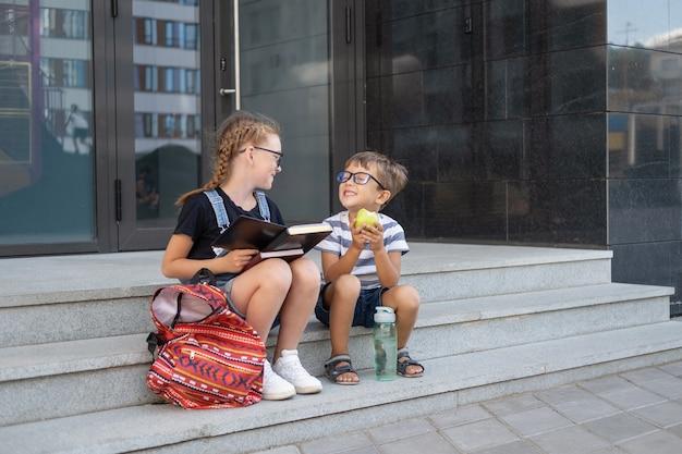 책과 배낭이 달린 안경을 쓴 두 명의 귀여운 백인 행복한 아이들. 앉아서 점심을 먹습니다. 방학. 지식의 날. 학교 개념으로 돌아가기.