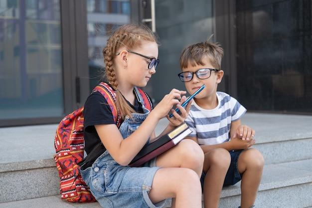 책과 배낭이 달린 안경을 쓴 두 명의 귀여운 백인 행복한 아이들. 앉아서 이야기하고 전화로 타이핑하십시오. 학교가 끝나고. 지식의 날. 학교 개념으로 돌아가기.