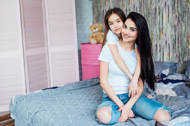 Две милые кавказские сестры, лежа на кровати