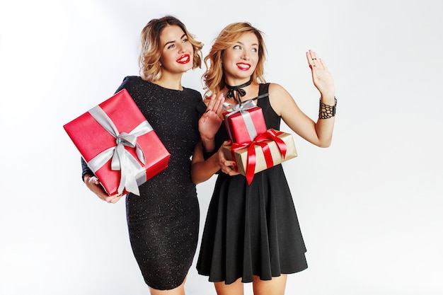 Two cute celebrating woman holding big new year gift boxes. surprise faces. wearing elegant black dress.