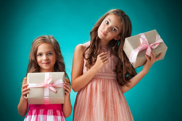 Two cute cheerful little girls with gift boxes