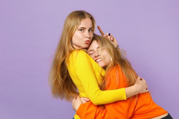 파스텔 바이올렛 파란색 벽에 고립 된 포옹 생생한 화려한 옷에 두 귀여운 쾌활 한 젊은 금발 쌍둥이 자매 여자. 사람들이 가족 라이프 스타일 개념.