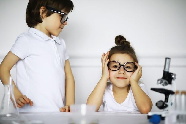 흰색 배경에 고립 된 실험을 만드는 화학 수업에서 두 귀여운 아이
