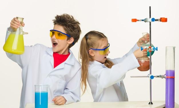 흰색 바탕에 실험을 하는 화학 수업에서 두 명의 귀여운 아이들