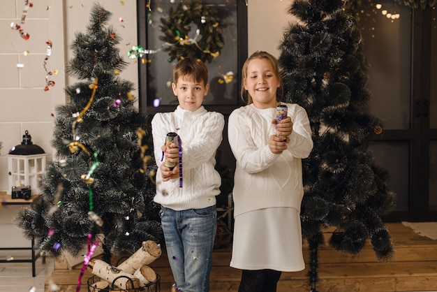 Two cute children on  background of christmas trees open crackers  have fun. bror  sister in white knitted sweaters celebrate   christmas in a bright house