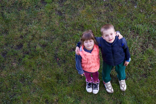 Two cute children boy and girl standing on green grass.