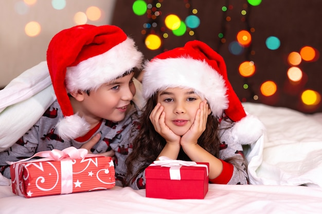 Two cute children, a girl and a boy, in pajamas and santa claus hats, cuddle on the white bed with gifts in their hands.