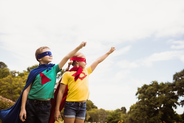 Two cute children pretending to fly in superhero costume