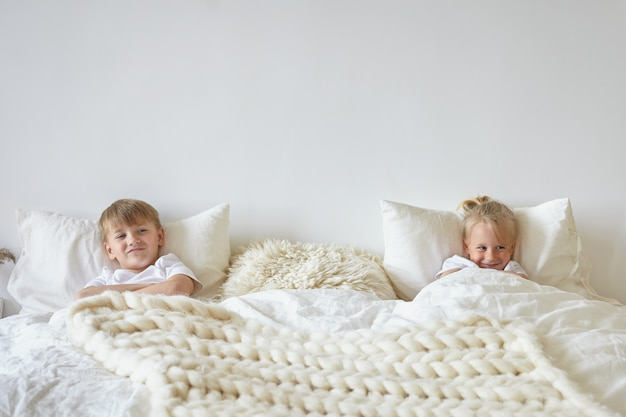 Two cute children relaxing in bedroom. indoor shot of teen boy in pajamas lying on bed with his blonde little brother on the other side, having playful looks. childhood, kids and family concept