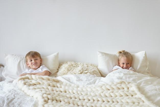 寝室でリラックスした2人のかわいい子供たち。遊び心のある表情で、反対側に彼の金髪の弟と一緒にベッドに横たわっているパジャマを着た十代の少年の屋内ショット。子供の頃、子供と家族の概念