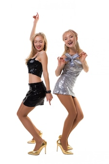 Two cute european twin girls dancing on a white in shiny dresses, isolated