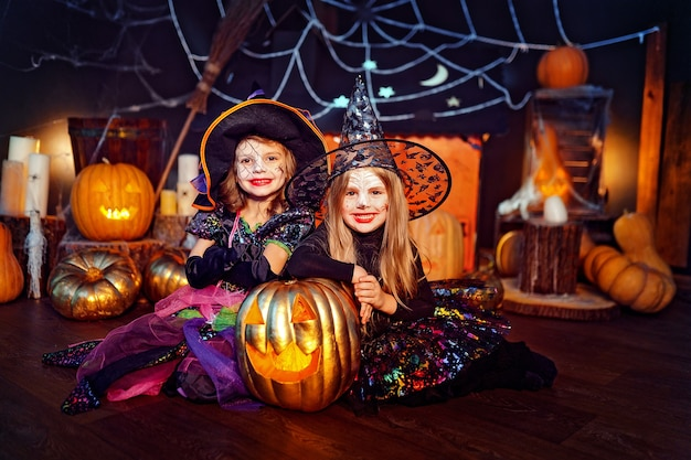 Two cute funny sisters celebrate the holiday. jolly children in carnival costumes ready for halloween in halloween decorations