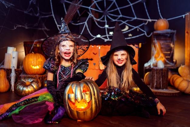 Две милые забавные сестры отмечают праздник. веселые дети в карнавальных костюмах готовы к хэллоуину в украшениях на хэллоуин