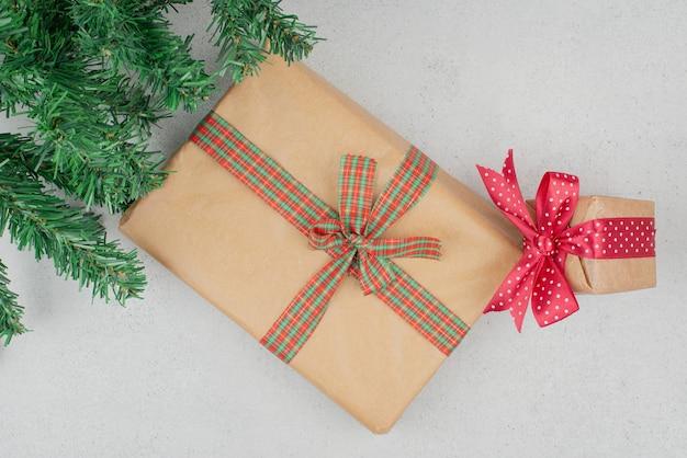 Две милые подарочные коробки с зеленой мишурой на серой поверхности.