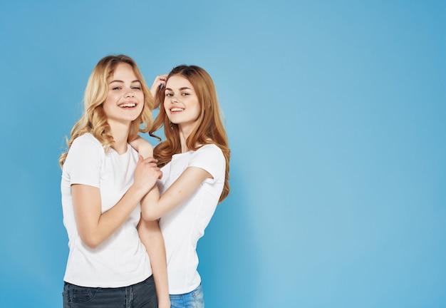 Две милые подруги в белых футболках стоят рядом с эмоциями дружбы на синем фоне