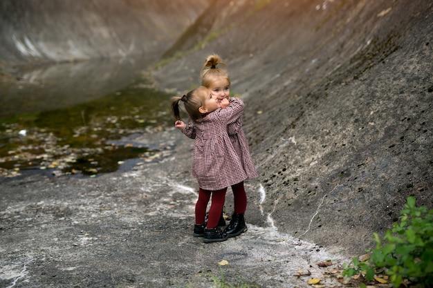 두 명의 귀여운 소녀가 바위가 많은 지역의 바위를 껴안고 있습니다