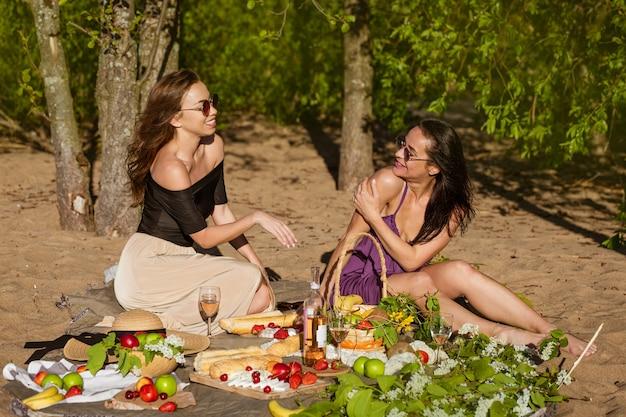 夏の元気な若い女性の毛布の上に座っている間、2人のかわいい女の子がピクニックで通信します...