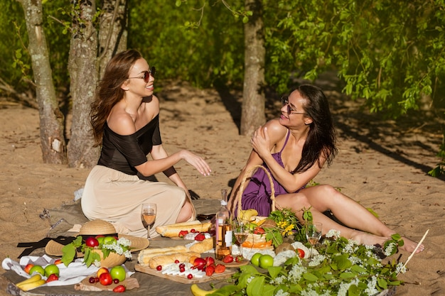 Two cute girls communicate on a picnic while sitting on a blanket in the summer cheerful young woman...