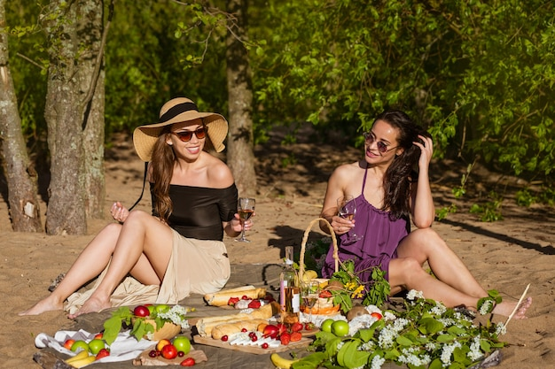 Two cute girls communicate on a picnic while sitting on a blanket