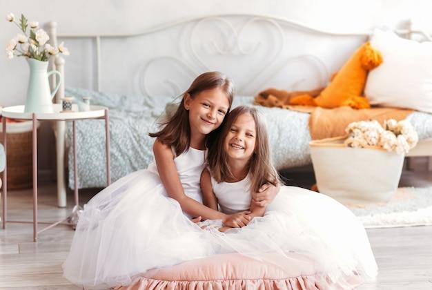 2人のかわいい女の子が明るい部屋に寄り添います。カメラで見て寝室で一緒に座っている子供たちの笑顔。兄弟愛