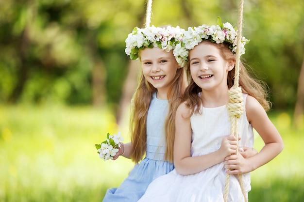 花の咲く古いリンゴの木の庭でブランコを楽しんでいる2人のかわいい女の子。晴れた日。子供のための春の野外活動