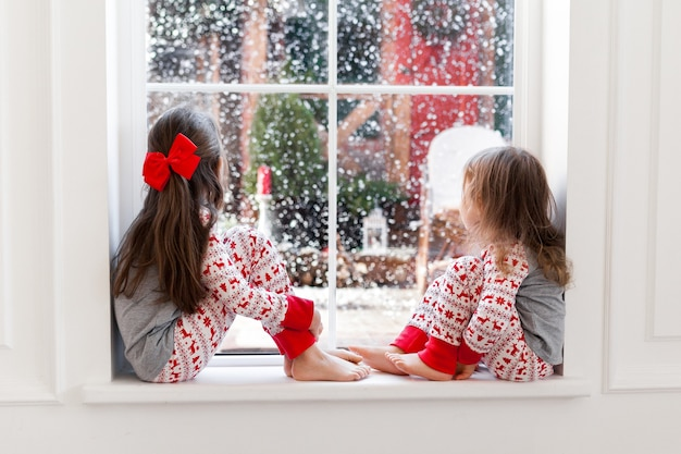 Two cute girls in pajamas sitting and looking out the window at snowy weather.