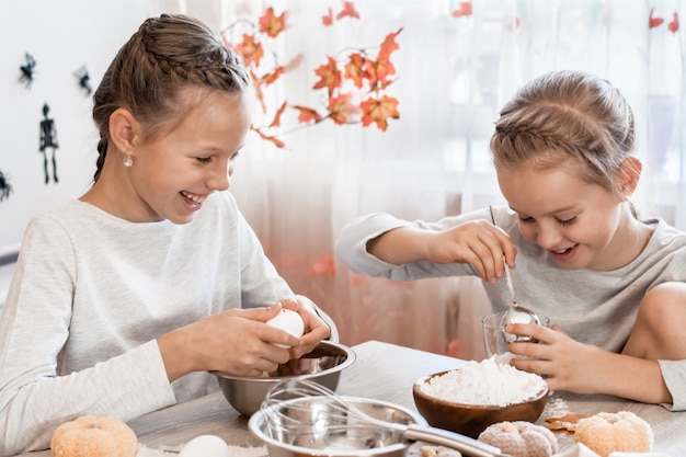 두 명의 귀여운 소녀가 집 부엌에서 할로윈 쿠키를 굽기 위해 계란과 밀가루를 진저브레드 반죽에 넣습니다. 할로윈 축하를 위한 간식 및 준비
