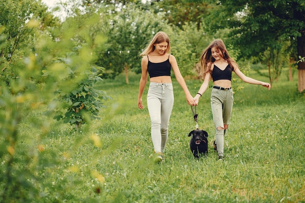 Two cute girls in a summer park with a dog