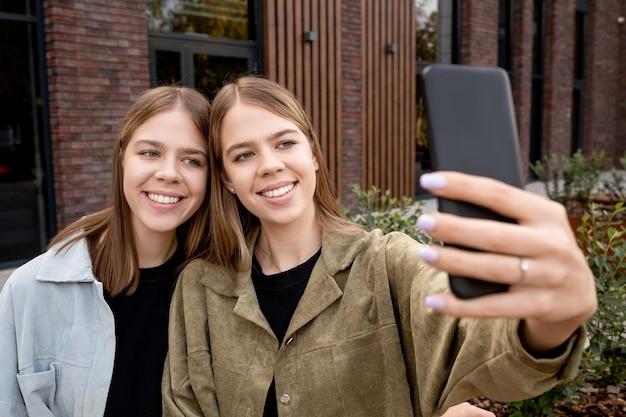 야외에서 셀카를 만드는 금발 머리를 가진 두 명의 귀여운 소녀
