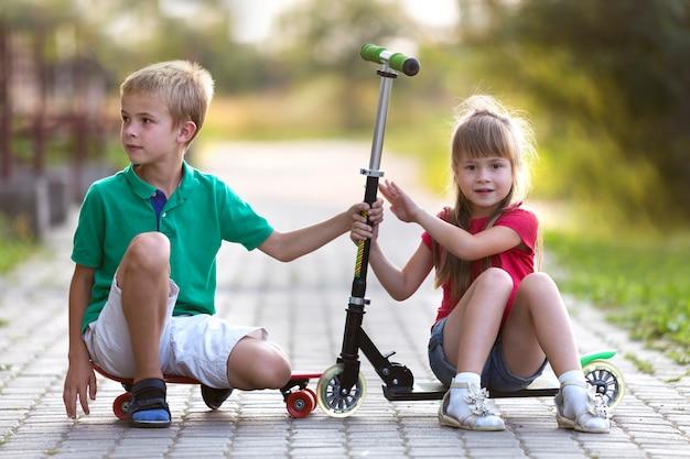 두 귀여운 행복 재미 웃는 어린 아이, 형제 및 자매, 카메라, 스쿠터와 잘 생긴 소년 포즈와 맑은 화려한 배경을 흐리게에 스케이트 보드에 앉아 꽤 긴 머리 소녀.