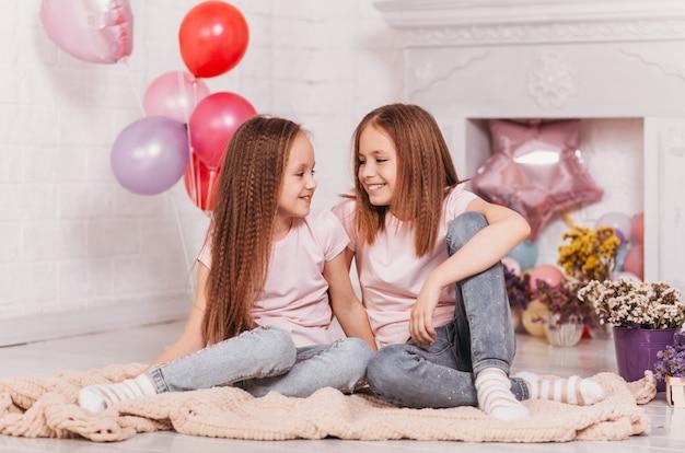 学齢期の2人のかわいい幸せな女の子が床に座ってお互いを見ています