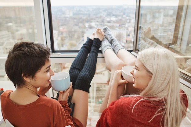 Two cute and happy woman sitting on balcony, drinking coffee and chatting with stretched legs that leaned on window. womanfriends talk about plans for today, wanting to skip work and stay home