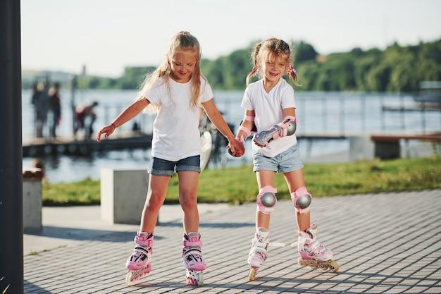 Двое симпатичных детей катаются на роликовых коньках в парке днем.