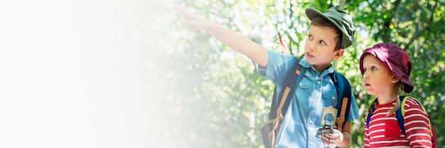 Due simpatici bambini che fanno trekking nel banner dello spazio di progettazione della foresta