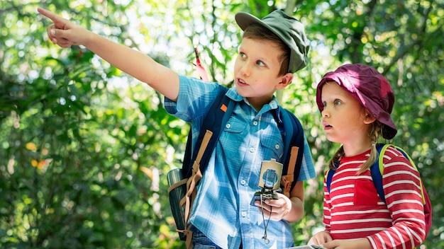森の中をトレッキングする2人のかわいい子供たち