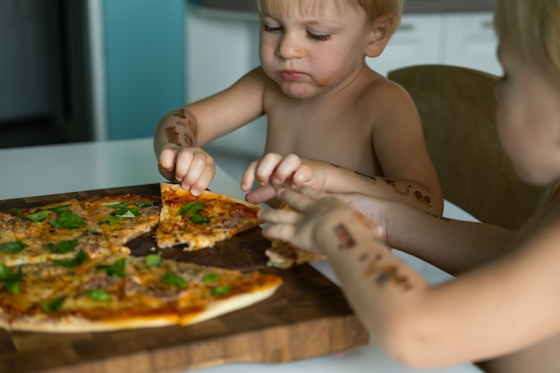 Two cute kids twins brothers boy eating home made pizza at kitchen at home.