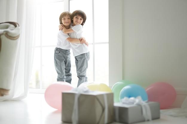 2人のかわいいラテンの双子の男の子、カジュアルな服装の小さな子供たちがお互いを抱きしめ、幸せそうに見え、カラフルな風船とギフトボックスのある部屋に立っています。休日、プレゼント、子供の頃のコンセプト