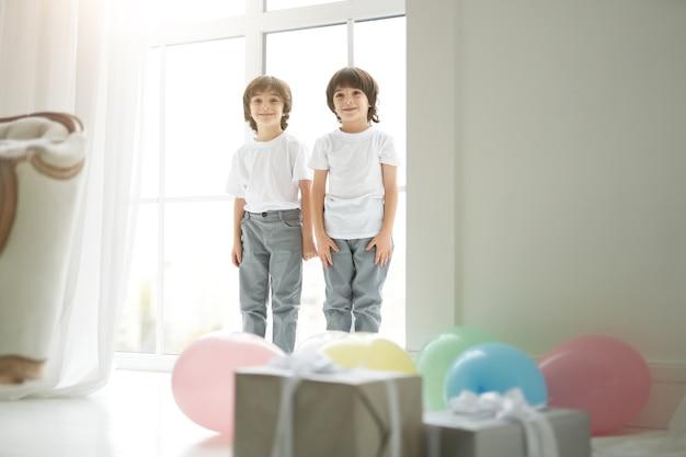 2人のかわいいラテンの双子の男の子、幸せそうに見えるカジュアルな服装の小さな子供たち、両親に挨拶し、カラフルな風船とギフトボックスを準備しています。休日、プレゼント、子供の頃のコンセプト