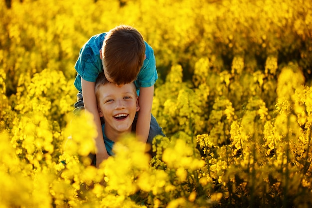 Two cute laughing boys hugging and having fun near the canola field.