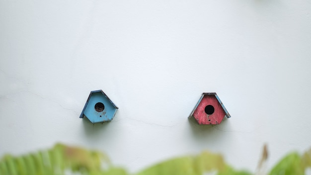 Two cute little birdhouses on the white wall