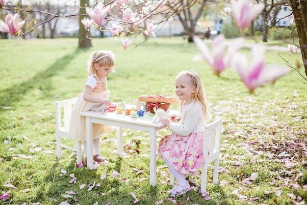 3 세의 두 귀여운 금발 소녀가 꽃이 만발한 목련 근처 공원에서 놀고 있습니다. 차 마시기. 부활절. 봄.