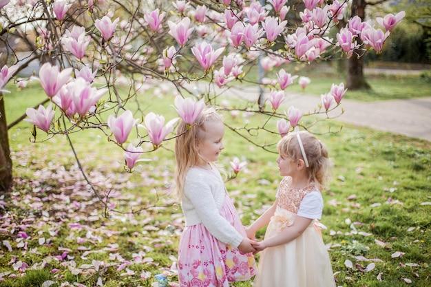 3歳の2人のかわいいブロンドの女の子が開花するマグノリアの近くの公園で遊んでいます。お茶を飲む。イースター。春。
