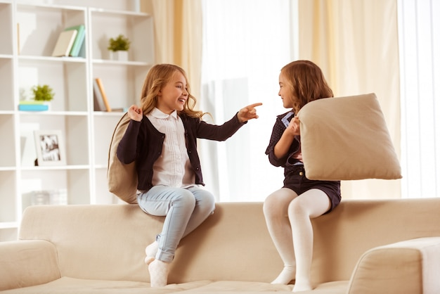 Two cute little girl sitting on back of white sofa at home.